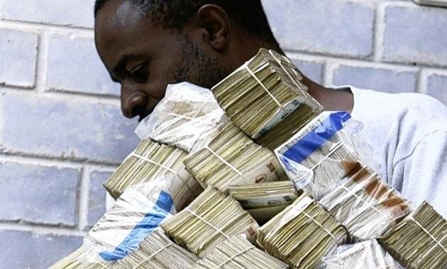 Seseorang membawa banyak uang dolar Zimbabwe